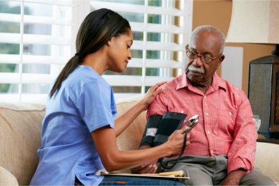caregiver monitoring elderly man's blood pressure