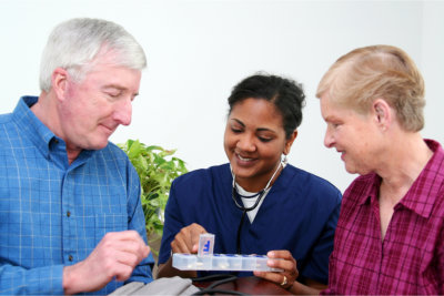 caregiver discussing about the medicine with elderly couple