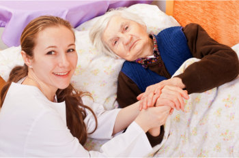 caregiver holding elderly woman's hand